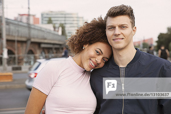 Portrait affectionate young couple on urban sidewalk
