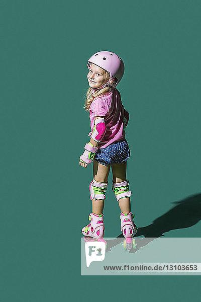 Portrait smiling girl roller skating against green background