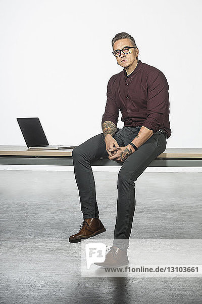 Portrait of man sitting on desk with laptop