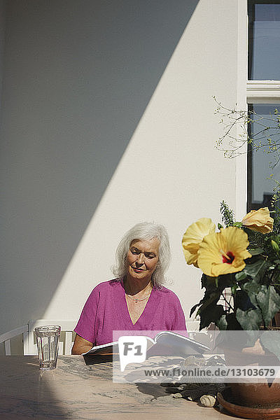 Senior woman reading magazine on sunny patio