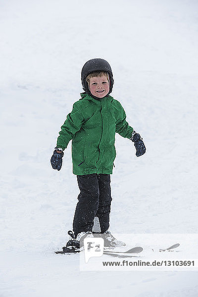 Portrait smiling  cute boy skiing in snow