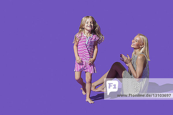 Portrait playful mother and daughter in striped dresses against purple background
