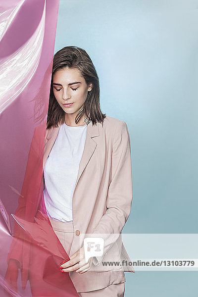 Portrait of a female fashion model posing with pink fabric and looking down