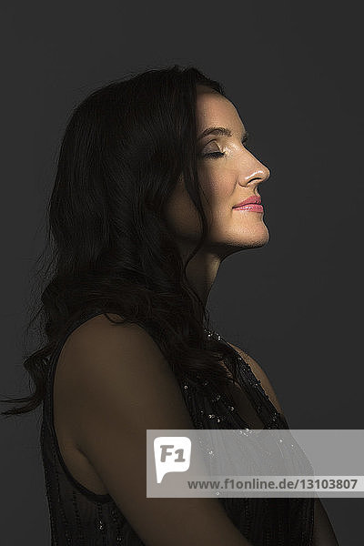Portrait of beautiful woman with eyes closed in side profile and amidst shadow