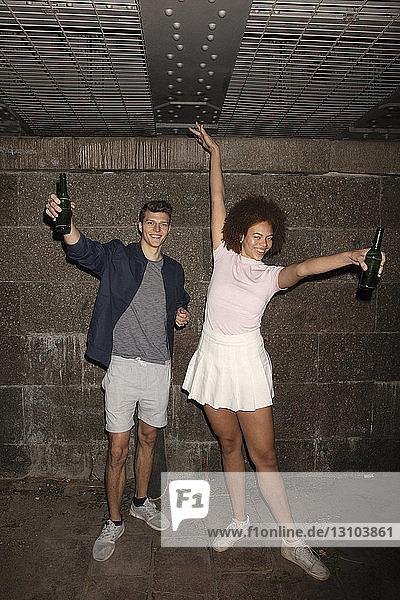 Portrait exuberant young couple drinking beer in basement