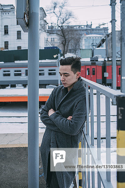 Young man in coat standing at winter railroad station