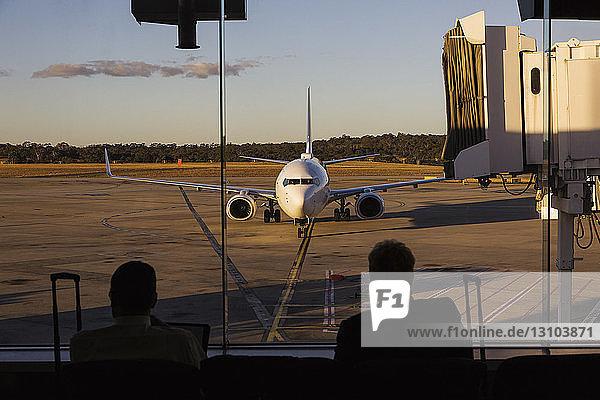 Airplane approaching passenger boarding bridge at airport