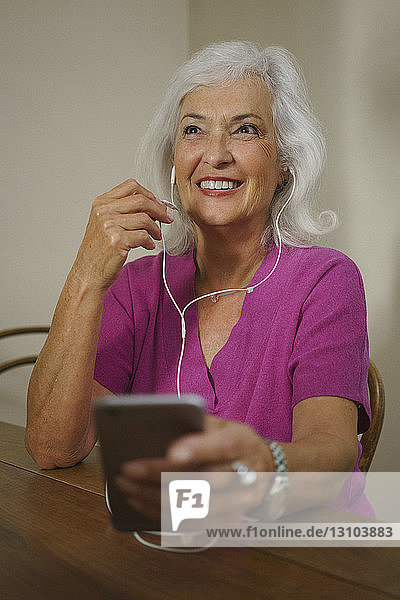 Smiling senior woman listening to music with headphones and mp3 player