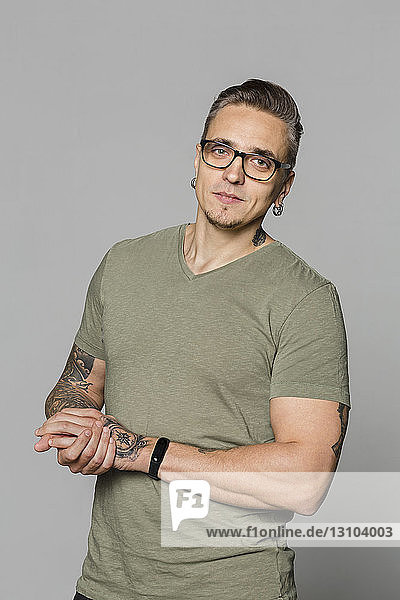 Portrait of man with glasses and hands clasped against gray background