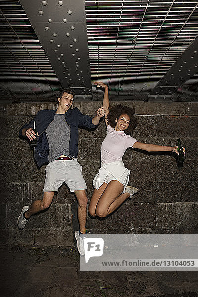 Portrait exuberant young couple drinking beer and jumping