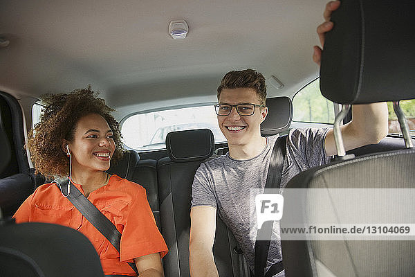 Happy young couple riding in back seat of car