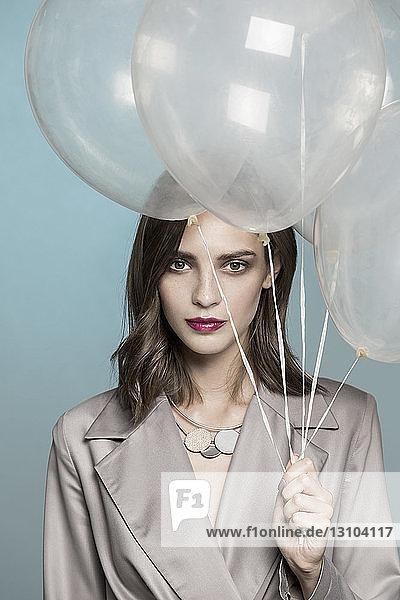 Portrait of female fashion model holding balloons