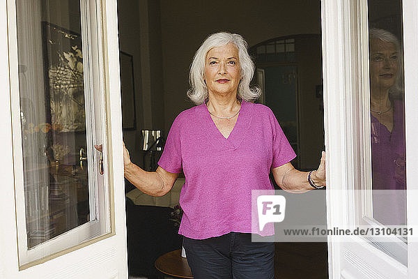 Portrait confident senior woman standing in patio doorway