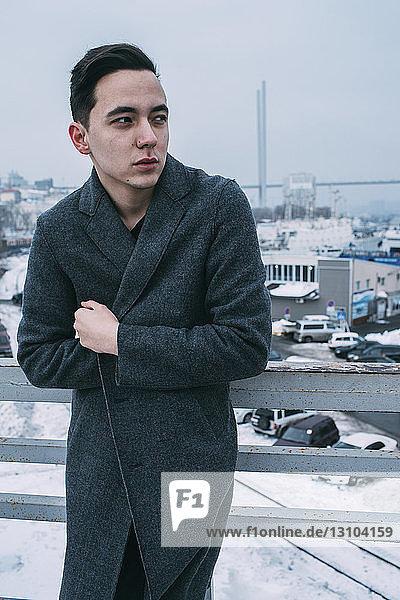 Young man in long coat on urban winter bridge