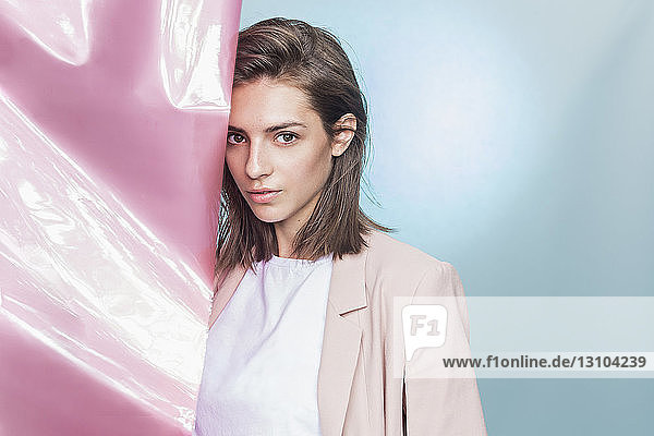 Portrait of a female fashion model posing with pink fabric