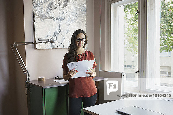 Portrait confident businesswoman with paperwork in office