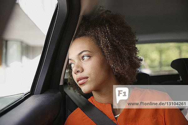 Thoughtful young woman riding in car  looking out window