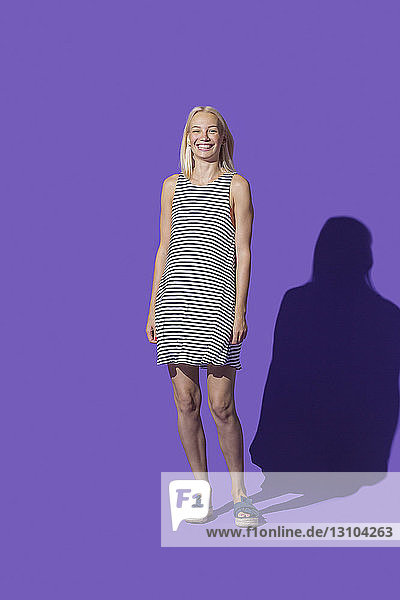 Portrait smiling woman in striped dress against purple background