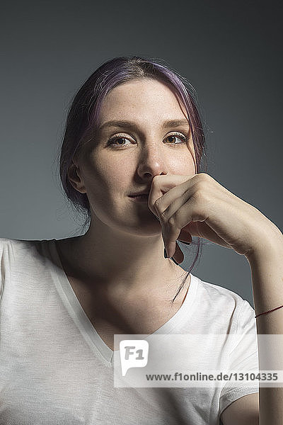 Portrait confident young woman against gray background