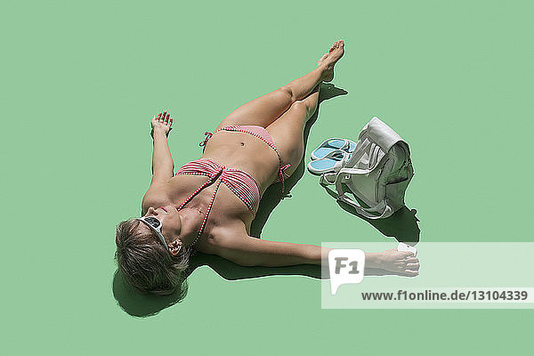 Woman in bikini sunbathing on green background