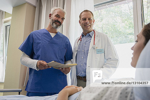 Doctors making rounds  talking with patient in hospital room