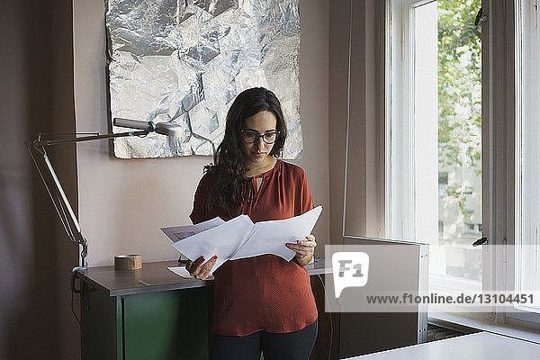 Businesswoman reading paperwork in office