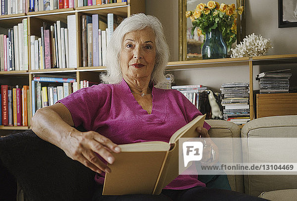Portrait confident senior woman reading book in living room