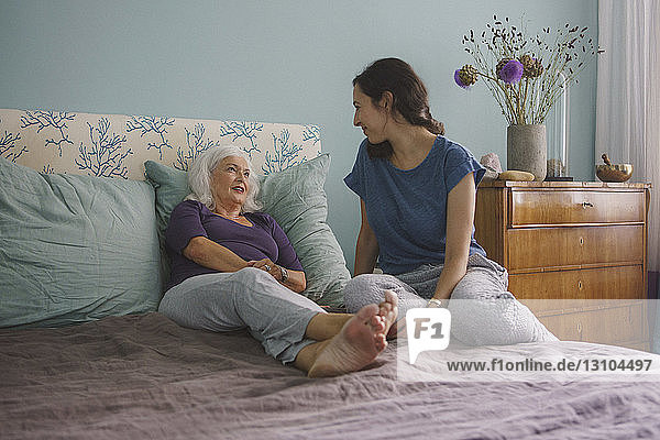 Senior mother talking with daughter on bed