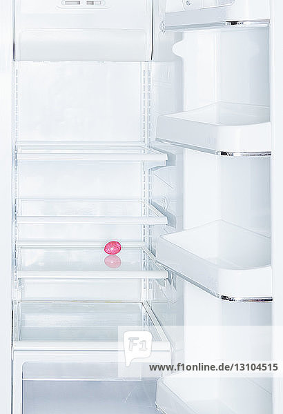 Pink Easter egg in open  empty white refrigerator