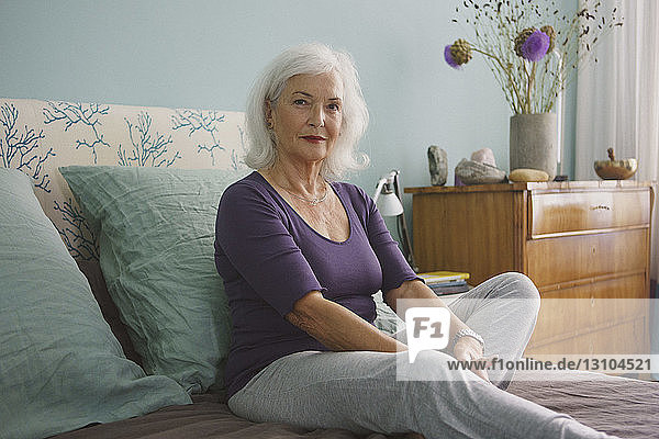 Portrait confident senior woman relaxing on bed