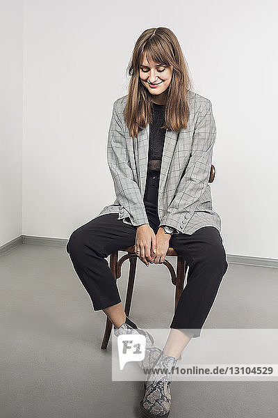 Portrait of stylish woman with long brown hair sitting on chair