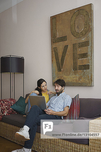 Couple using laptop on living room sofa