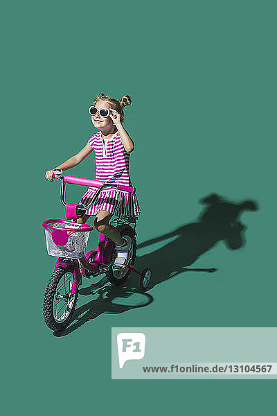 Girl in sunglasses bike riding against green background