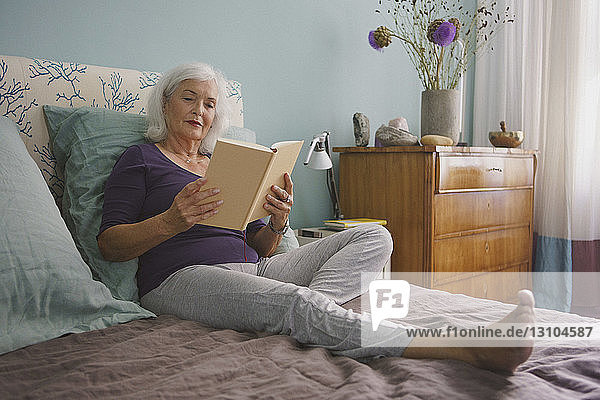 Senior woman reading book on bed