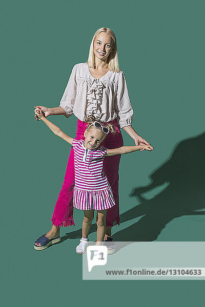 Portrait mother and daughter holding hands against green background