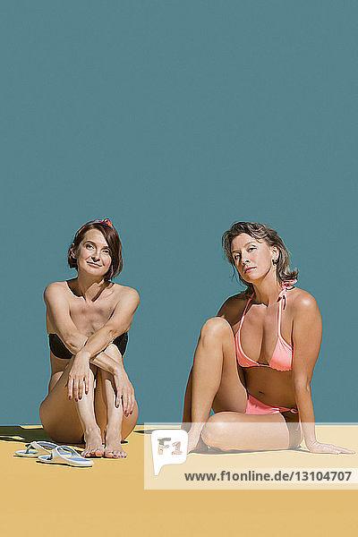 Portrait confident women sunbathing in bikinis