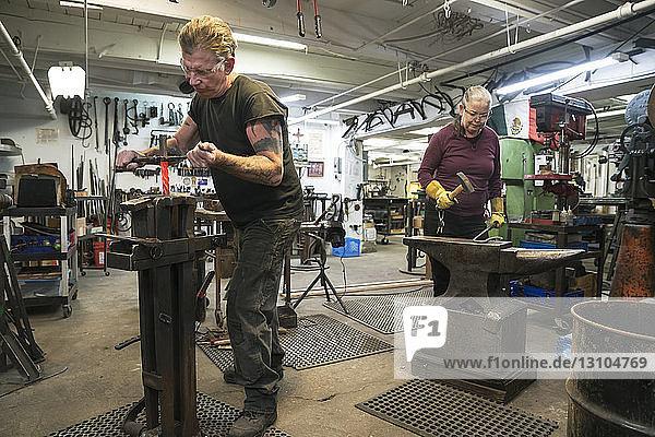 Kaukasische Schmiedinnen und Schmiede  Metallarbeiter bei der Arbeit in ihrer Atelierwerkstatt