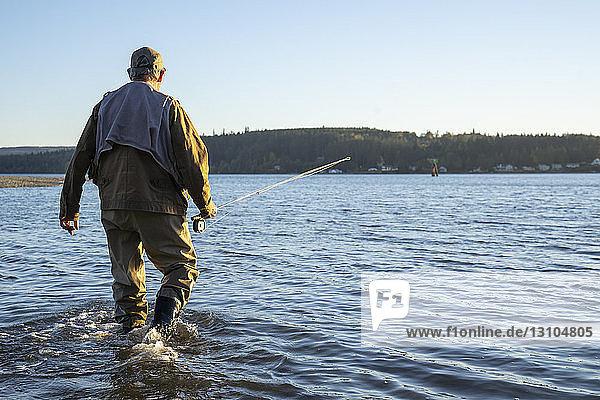 Ein Fliegenfischer  der zu einer neuen Position im flachen Salzwasser geht  während er an der Küste nach Cutthroat-Forellen und Lachsen fischt.