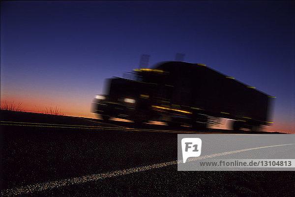 Ein Schlafwagen  der sich bei Sonnenaufgang als Silhouette auf der Straße abzeichnet  ein orangefarbenes Licht am Horizont.