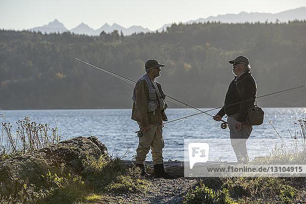 Zwei Fliegenfischer unterhalten sich an einem Salzwasserstrand im Nordwesten des Bundesstaates Washington über Techniken zum Fischen