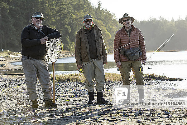 A portrait of two Caucasian male fly fishermen and their fly fishing guide standing on a beach on the west coast of the USA