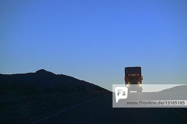 Ein Lastwagen der Klasse 8 bildete eine Silhouette  als er auf der Autobahn über einen Hügel kam.