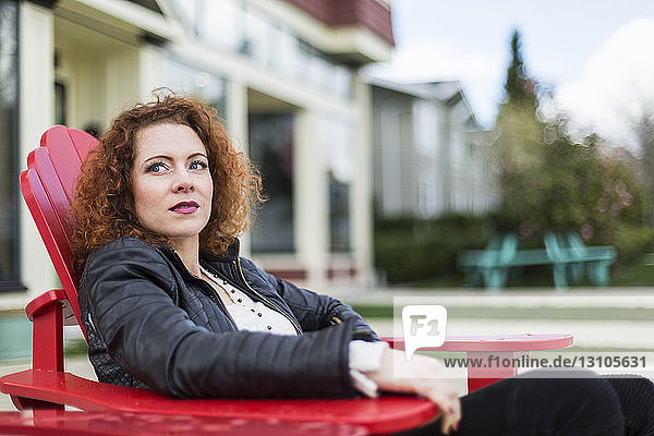 Portrait of a woman with red  curly hair sitting outdoors in springtime; North Vancouver  British Columbia  Canada