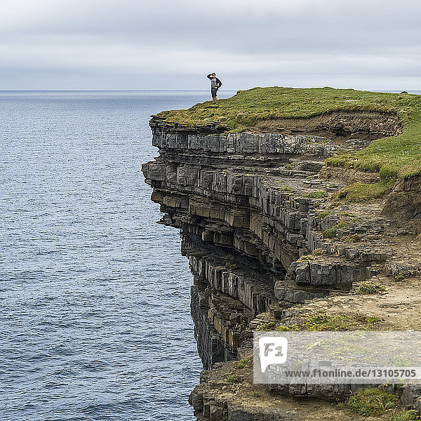 A male tourist stands looking out over the ocean from Downpatrick Head,  West coast of Ireland; Killala,  County Mayo,  Ireland