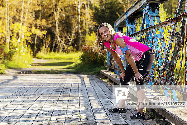 An attractive middle-aged woman pauses to rest on a bridge during a run on a beautiful warm fall evening in a city park; Edmonton  Alberta  Canada