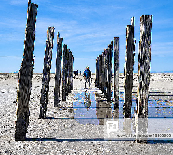 Reflection of a man in shallow water standing on a barren landscape with wooden posts in a row on either side of him  Great Salt Lake; Utah  United States of America