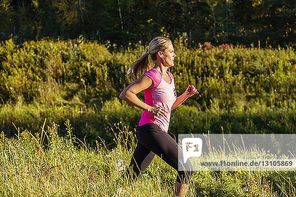 An attractive middle-aged woman wearing active wear and listening to music runs along a creek in a city park at sunset on a warm autumn evening; Edmonton  Alberta  Canada