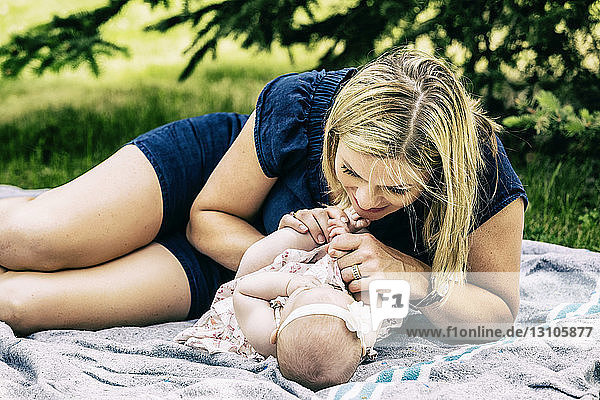 A young mother playing with her baby on a blanket in a city park on a warm summer day; Edmonton  Alberta  Canada