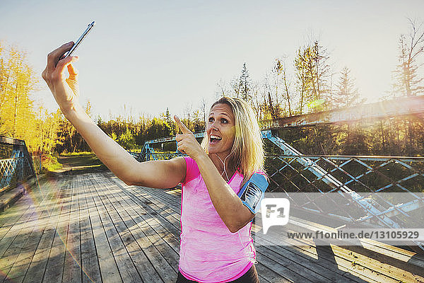 A woman wearing active wear and an arm band for her cell phone stands on a bridge in a park in autumn taking a self-portrait with her cell phone; Edmonton  Alberta  Canada