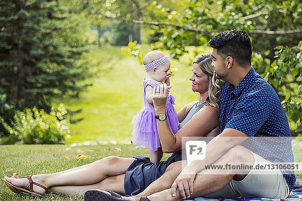 A mixed race husband and wife relax together with their baby girl on a blanket in a park on a warm autumn afternoon; Edmonton  Alberta  Canada